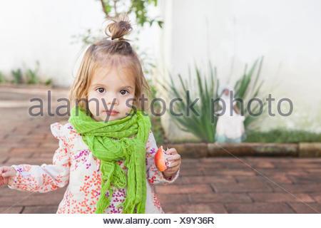Baby girl mangiando frutta all'aperto Foto Stock
