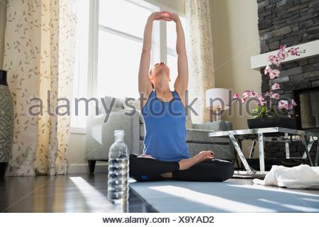 Donna matura con le braccia sollevate a praticare lo yoga del tappetino Foto Stock