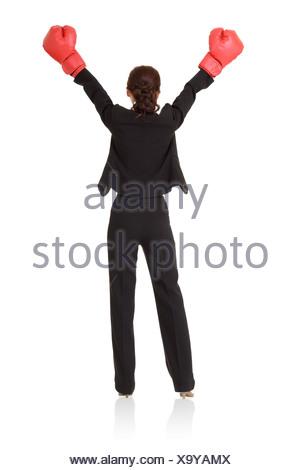 Vincitore, donna d'affari di successo di alzare la mano con il rosso guantoni da pugilato, vista posteriore a piena lunghezza ritratto isolato su sfondo bianco Foto Stock