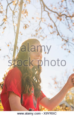 La Svezia Sodermanland, Stigtomta, ragazza adolescente (14-15) seduto su albero oscillare in presenza di luce solare Foto Stock