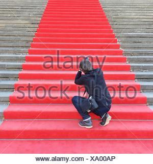 Vista posteriore di un maschio di Paparazzi sulla moquette rossa scale Foto Stock
