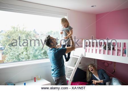 Padre affettuoso di sollevamento figlia dei bimbi in camera da letto Foto Stock