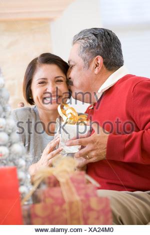 Coppia di mezza età seduta con affetto e tenendo presente il Natale Foto Stock