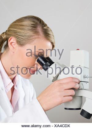Donna scienziato utilizzando un microscopio Foto Stock