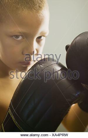 Ragazzo che indossa guantoni da pugilato Foto Stock