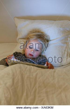Boy utilizzando una compressa a letto Foto Stock