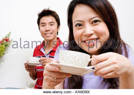 Ritratto di una giovane donna e una metà uomo adulto bere il tè Foto Stock