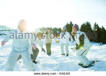 Giovani amici in esecuzione nella neve, vestito in abiti invernali Foto Stock