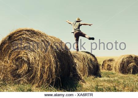 Vista posteriore di un uomo in equilibrio su una gamba sulla parte superiore di una balla di fieno. Foto Stock