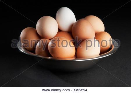 Close-up di un uovo di colore bianco sulla parte superiore delle uova di colore marrone Foto Stock