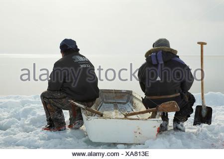 Due saldatori Inuit seduti a bordo di ghiaccio sulla loro barca a remi e si affacciano sul mare aperto, Groenlandia, Ostgroenland, Tunu, Kalaallit Nunaat, Scoresbysund, Kangertittivag, Kap Tobin, Ittoqqortoormiit Foto Stock