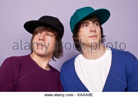 Due ragazzi adolescenti Indossando cappellini da baseball lo sguardo lontano, studio shot Foto Stock