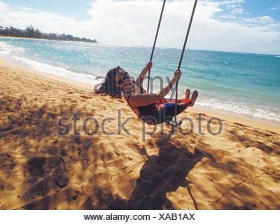 Donna sulla spiaggia Swing Foto Stock