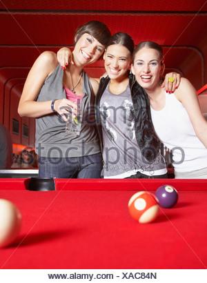 Tre donne in piedi da tavolo da biliardo sorridente Foto Stock