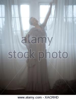 Una donna che indossa un lungo abito grigio, dietro una cortina di voile