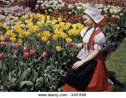 dd5ccca1f1c4 Una ragazza che indossa un tradizionale abito olandese guarda i tulipani in  un giardino. Foto