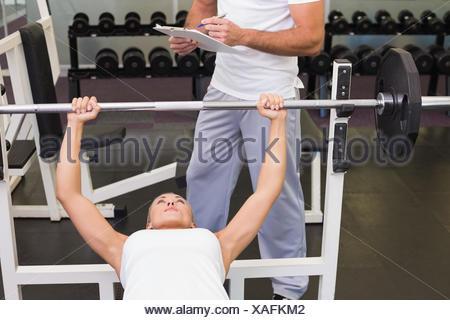 Trainer con appunti oltre alla donna il sollevamento barbell in palestra Foto Stock