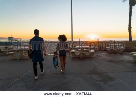 Giovane camminare vicino a spiaggia, azienda di skateboard, vista posteriore Foto Stock