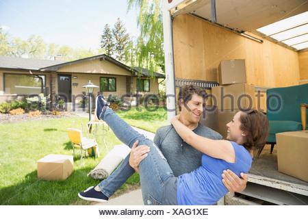 Uomo che porta la donna al di fuori spostando van Foto Stock