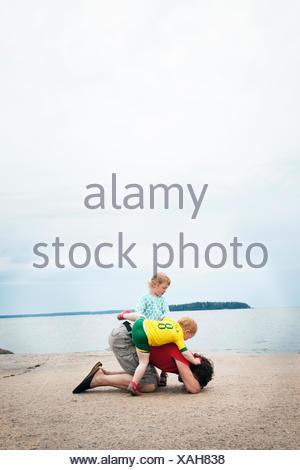Padre giocare con figli (2-3, 4-5) sulla spiaggia Foto Stock
