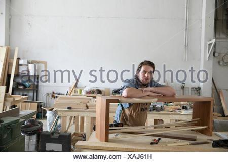 Ritratto fiduciosi, gravi falegname maschio appoggiata sul banco di legno in officina Foto Stock