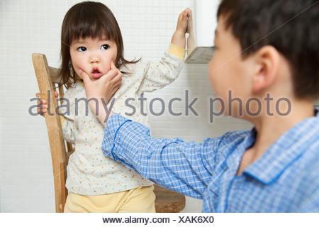 Maliziosa fratello holding giovani suore faccia Foto Stock