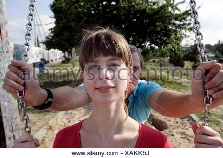 Uomo Donna di spinta sul parco giochi swing Foto Stock