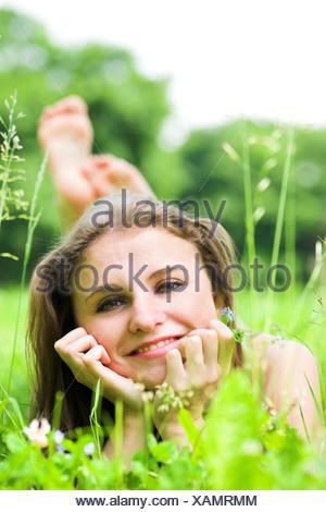 Ragazza fissa sull'erba con fiori Foto Stock