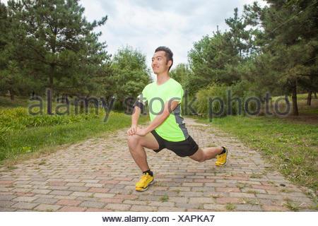 Giovane maschio runner stretching gambe in posizione di parcheggio Foto Stock