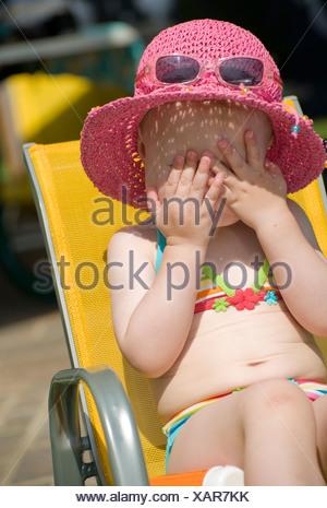 Bambina in un bikini con un cappello per il sole seduti in un seggiolino per bambino tenendo le mani davanti ai suoi occhi Foto Stock