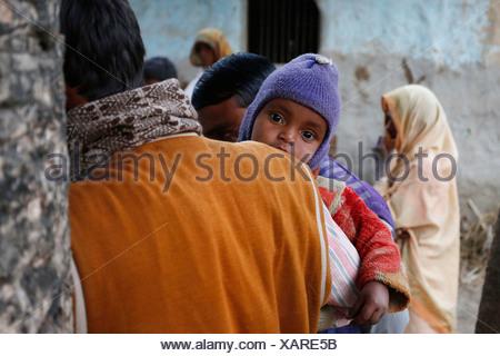 Un giovane bambino sul braccio di suo padre, gli abitanti di un villaggio vicino Rajbiraj, Terai regione, Nepal, Asia Foto Stock