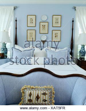 https://l450v.alamy.com/450vit/xat5fr/piccolo-divano-blu-ai-piedi-del-letto-con-girata-mandrini-e-cuscini-blu-in-blu-pallido-camera-da-letto-xat5fr.jpg