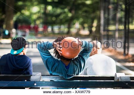 Giovani uomini seduti sul parco, una holding basket Foto Stock