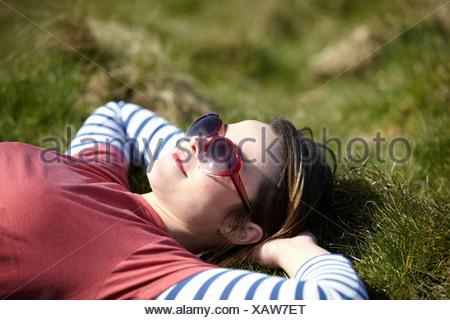 Giovane donna indossa forma di cuore occhiali da sole sdraiati sull'erba Foto Stock