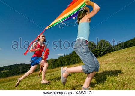 Due ragazze in esecuzione con un aquilone in un prato nella Foresta Nera, Baden-Wuerttemburg, Germania, Europa Foto Stock