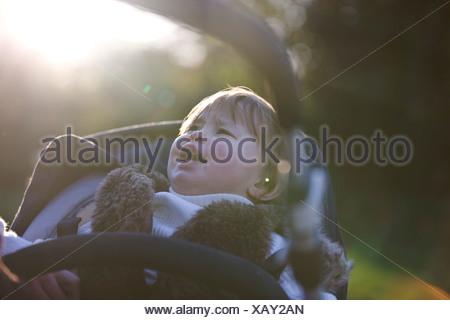 Una bambina che grida nel suo passeggino Foto Stock
