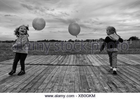 Due ragazze che giocano all'aperto con palloncini Foto Stock
