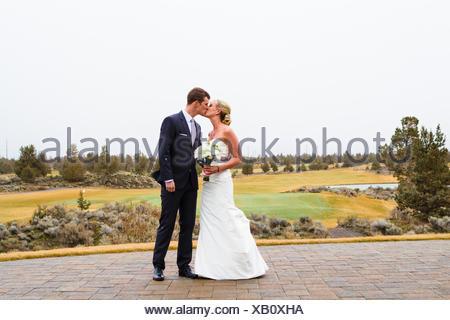 Sposo e sposo baciando il giorno del matrimonio, Oregon, Stati Uniti Foto Stock