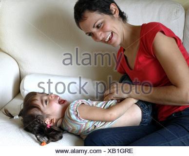 Madre seduti sul divano solletica la figlia Foto Stock