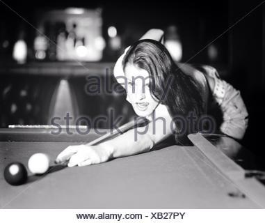 Giovane donna mirando a sfera con tavolo da biliardo Foto Stock