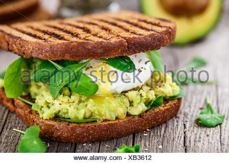Sandwich alla griglia con avocado, uovo in camicia e rucola sul tavolo di legno Foto Stock