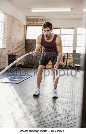 L'uomo esercita con combattendo la corda Foto Stock