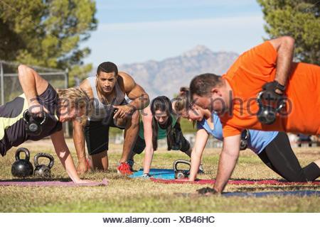 Istruttore di Fitness con persone che esercitano in outdoor bootcamp Foto Stock