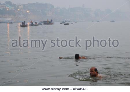 I nuotatori indiano all'alba nel fiume Gange, Varanasi, Uttar Pradesh, India, Asia Foto Stock