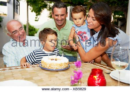 Famiglia soffiando candele fuori sulla torta Foto Stock