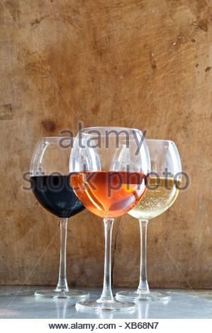 Rose, vini bianchi e rossi in bicchieri Foto Stock
