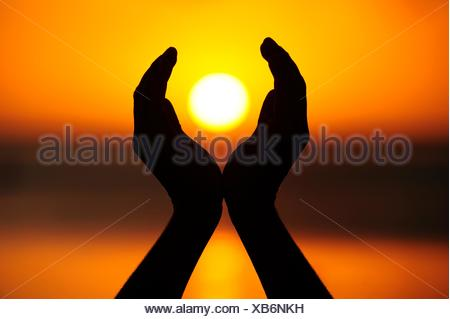 Due mani tenendo il sole al tramonto, La Gaulette, Mauritius Foto Stock