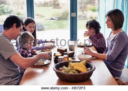 Famiglia avente la cena insieme a tavola Foto Stock