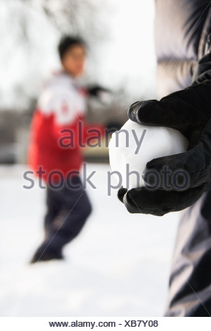 Ragazzo holding snowball pronto a lanciare a boy in background Foto Stock
