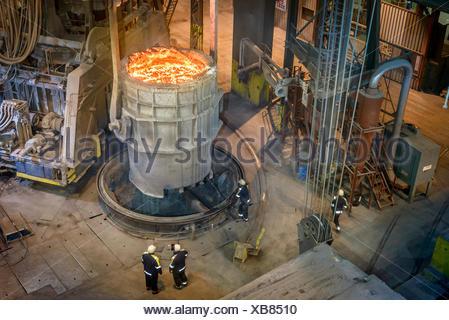 Angolo di alta vista di lavoratori siderurgici ispezione di acciaio fuso in pallone Foto Stock